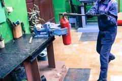 Een mens die industriële ondeugd met een reusachtige gasmoersleutel werken schroeft een noot op een rode brandblusapparaatcilinde royalty-vrije stock afbeelding