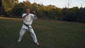 Een mens die in kimono het praktizeren karate, een reeks die schoppen doen, in de ochtend in het stadspark opleiden stock video