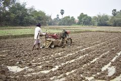 Een mens die Land door een hand, padiegebied, met de hand tractor cultiveren royalty-vrije stock fotografie