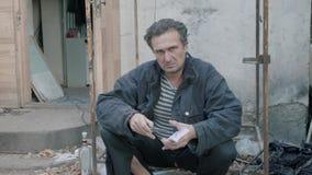 Een mens die een mes en een geld houden Het onderzoeken van de camera stock video