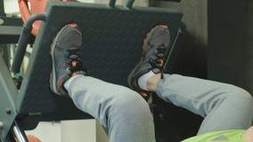 Een mens die met bovenmatig gewicht beenpersen op de simulator in de gymnastiek doen De mens van de geschiktheid training Gezond  stock footage
