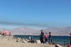 Een mens die met een quadrocopter op het strand in Eilat spelen Stock Foto's