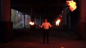 Een mens die met make-upskelet Halloween twee toortsen met een sterke vlam houden stock videobeelden