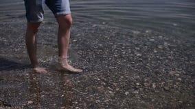 Een mens die met naakte voeten gaat naar het strand lopen stock video