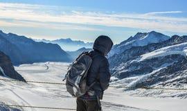 Een mens die met rugzak op sneeuwpiek genieten van royalty-vrije stock foto