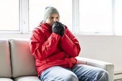 Een Mens die met Warme Kleding de Koude binnen Huis op de bank voelen stock fotografie
