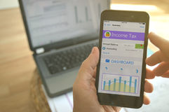 Een mens die mobiele app gebruiken om zijn inkomstenbelasting te berekenen stock afbeeldingen