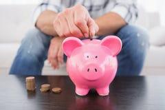 Een mens die muntstukken in spaarvarken zetten Stock Foto