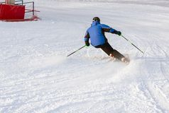 Een mens die onderaan skihelling ski?en royalty-vrije stock afbeelding