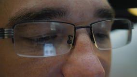 Een mens die op een bed liggen die glazen dragen communiceert op een smartphone stock video