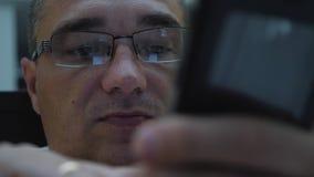 Een mens die op een bed liggen die glazen dragen communiceert op een smartphone stock videobeelden