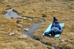 Een mens die op geel gras ligt Royalty-vrije Stock Foto