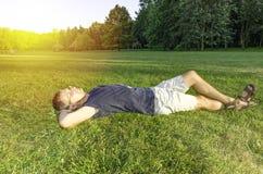 Een mens die op het gras met een smartphone ontspannen Royalty-vrije Stock Afbeeldingen