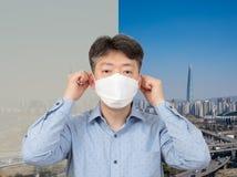 Een mens die op middelbare leeftijd een masker op de achtergrond van een stadshoogtepunt dragen van fijn stof stock foto