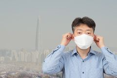 Een mens die op middelbare leeftijd een masker op de achtergrond van een stadshoogtepunt dragen van fijn stof royalty-vrije stock foto's
