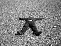 Een mens die op stenen ligt Royalty-vrije Stock Fotografie