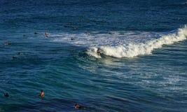 Een mens die op witte schuimgolf surfen in blauwe oceaan met mensen het zwemmen royalty-vrije stock foto's