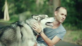 Een mens die in park een hond strijken stock videobeelden