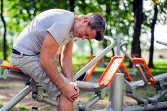 Een mens die pijn in zijn knie tijdens sport en training in p voelen stock afbeelding