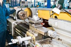 Een mens die in een robe, overall werken bevindt zich naast een industriële draaibank voor knipsel, die messen van metalen, hout  stock fotografie