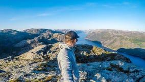 Een mens die een selfie nemen en langs een fjord in Noorwegen wandelen stock foto