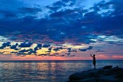 Een mens die tijdens zonsondergang vissen Stock Foto