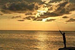 Een mens die tijdens zonsondergang vissen Royalty-vrije Stock Foto's