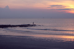 Een mens die tijdens zonsopgang vissen Stock Afbeeldingen
