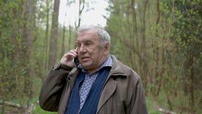 Een mens die van leeftijd, in het park lopen en op zijn mobiele telefoon spreken In avondtijd stock videobeelden