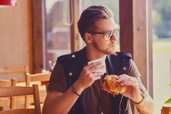 Een mens die een veganisthamburger eten stock afbeelding