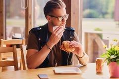 Een mens die een veganisthamburger eten royalty-vrije stock afbeeldingen