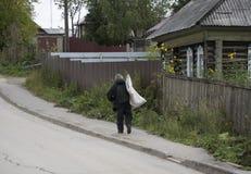 Een mens die een weerspiegelend vest dragen die huisvuil in zijn stad opnemen royalty-vrije stock foto's