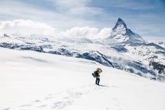 Een mens die zich op de sneeuw bevinden die de achtergrond van Matterhorn bekijken Stock Foto's