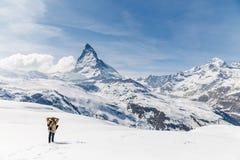 Een mens die zich op de sneeuw op de achtergrond van Matterhorn bevinden Royalty-vrije Stock Fotografie