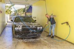 Een mens die zijn auto in autowasserettebaai wassen stock afbeelding
