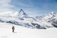 Een mens die zijn hand golven die zich op de sneeuw op de achtergrond van Matterhorn bevinden Stock Afbeeldingen