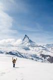 Een mens die zijn hand golven die zich op de sneeuw op de achtergrond van Matterhorn bevinden Royalty-vrije Stock Afbeelding