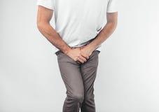 Een mens die zijn penis met op de witte achtergrond houden Wil naar het toilet gaan stock afbeeldingen