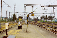 Een mens die zijn trein in spoorplatform zoeken Stock Foto's