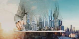 Een mens digitale tablet gebruiken, en modern gebouwenhologram die Onroerende goederenzaken en bouwtechnologieconcept