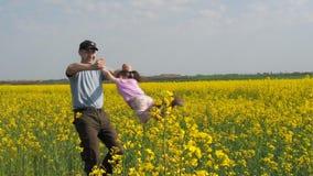 Een mens draait een kind De papa draait zijn dochter in geel Een gelukkige familie Koolzaad, Canola, Biodieselgewas stock videobeelden