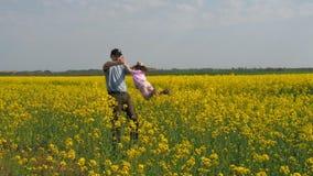 Een mens draait een kind De papa draait zijn dochter in geel Een gelukkige familie Koolzaad, Canola, Biodieselgewas stock footage