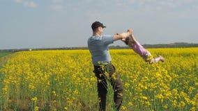 Een mens draait een kind De papa draait zijn dochter in geel Een gelukkige familie Koolzaad, Canola, Biodieselgewas stock video