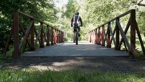 Een mens drijft langs een brug in een park, op een fiets In de zomertijd stock video