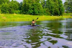 Een mens drijft op een kajak nave Stock Fotografie