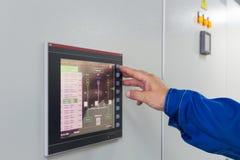 Een mens drukt een knoop bij de controle van het kleurenscherm Stock Foto