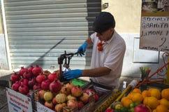 Een mens drukt granaatappel in de Historische Capo-markt in Palermo, Sicilië stock afbeeldingen