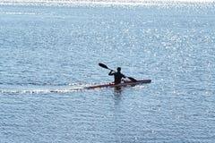 Een mens in een duikkostuum op een kajak drijft royalty-vrije stock afbeelding