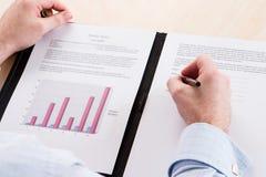 Een mens in een blauw overhemd dat een contract ondertekent Stock Afbeeldingen