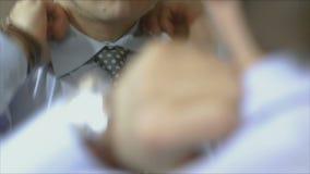 Een mens in een blauw overhemd om een band in de spiegel te binden stock footage